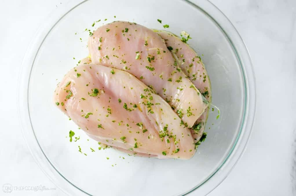 Raw chicken in a clear bowl marinading
