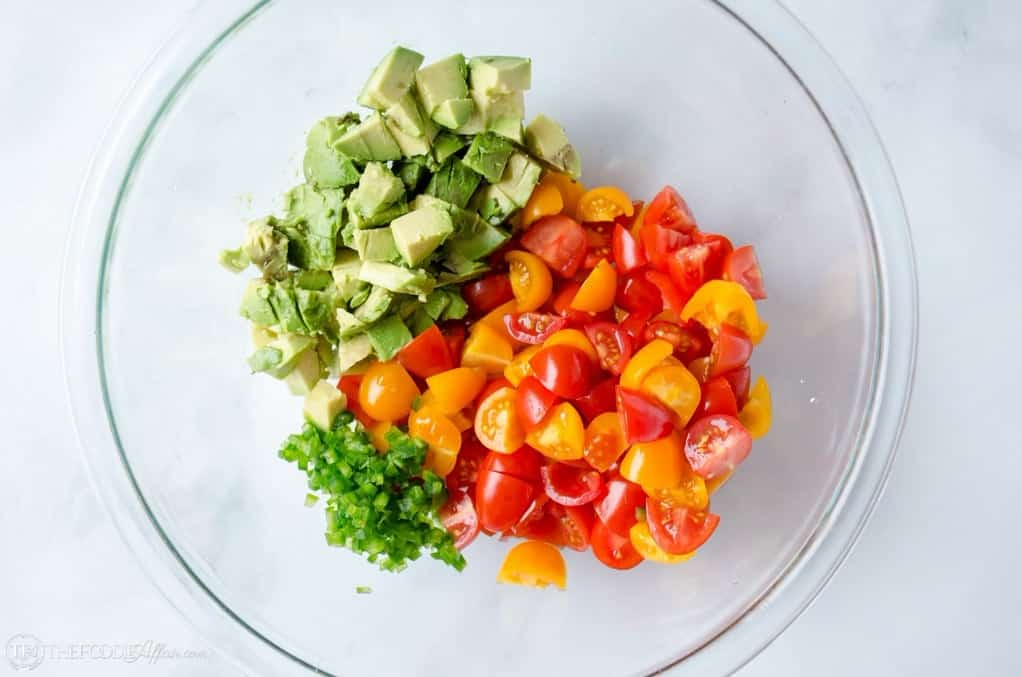 chopped ingredients in clear bowl for chicken and avocado dish