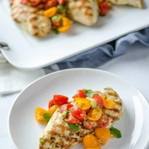 grilled chicken and avocado salsa on a white plate
