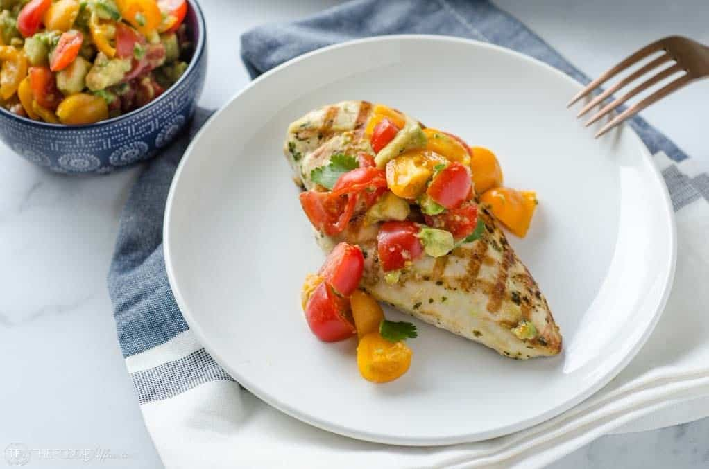 grilled chicken and avocado salsa on a white plate with blue napkin