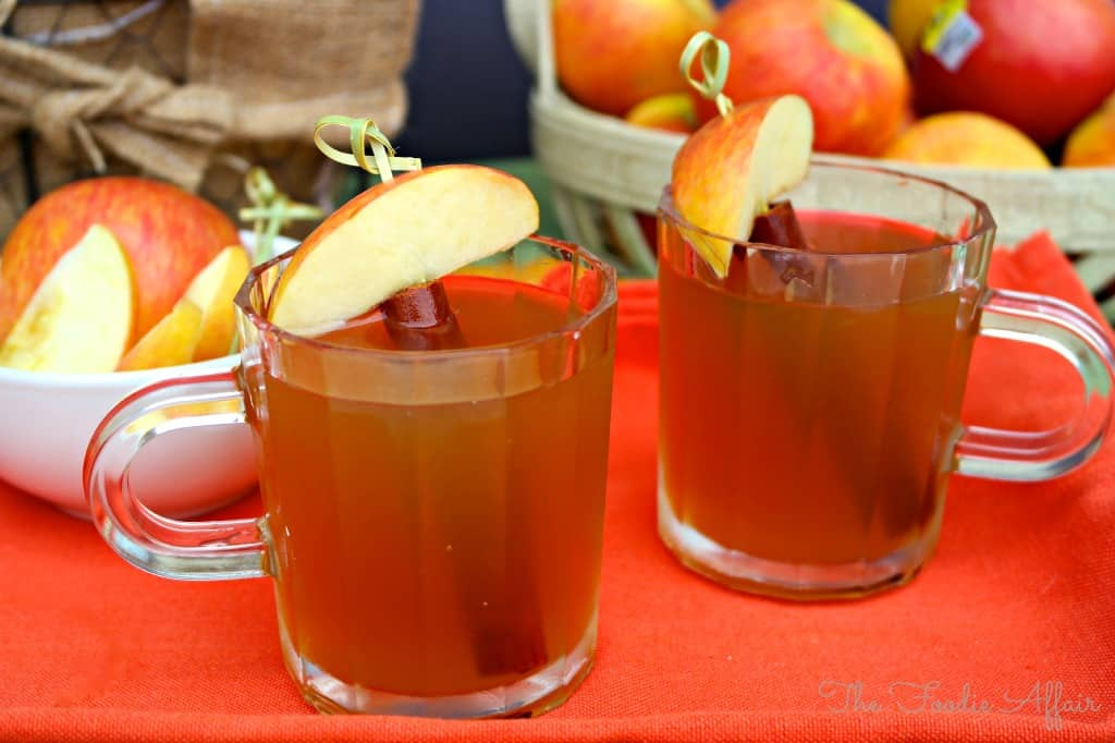 Two clear mugs filled with apple pie moonshine