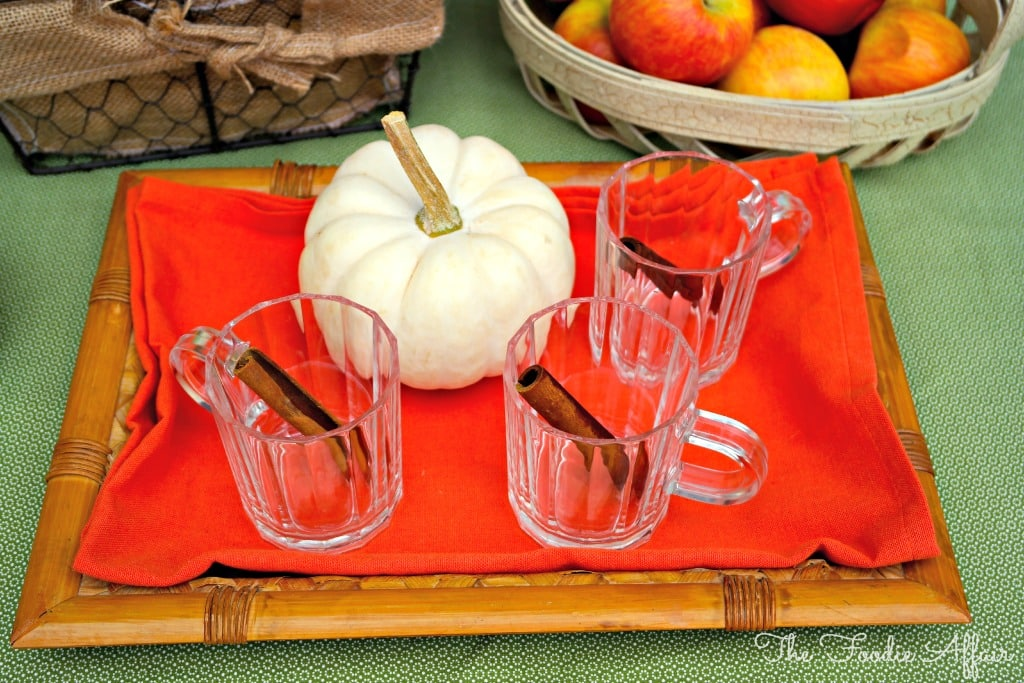clear glasses on a bamboo tray with cinnamon sticks for apple pie moonshine