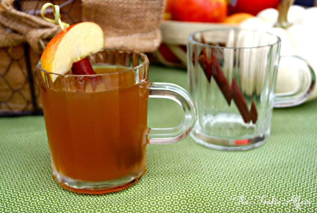 a clear glass filled with apple pie moonshine with fresh apple