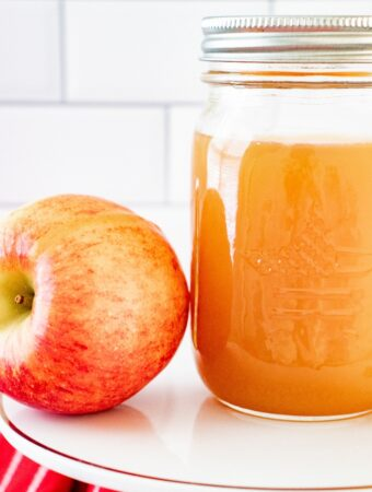 A clear mason jar with homemade apple pie moonshine on a white cake plate with a fresh apple on the side.