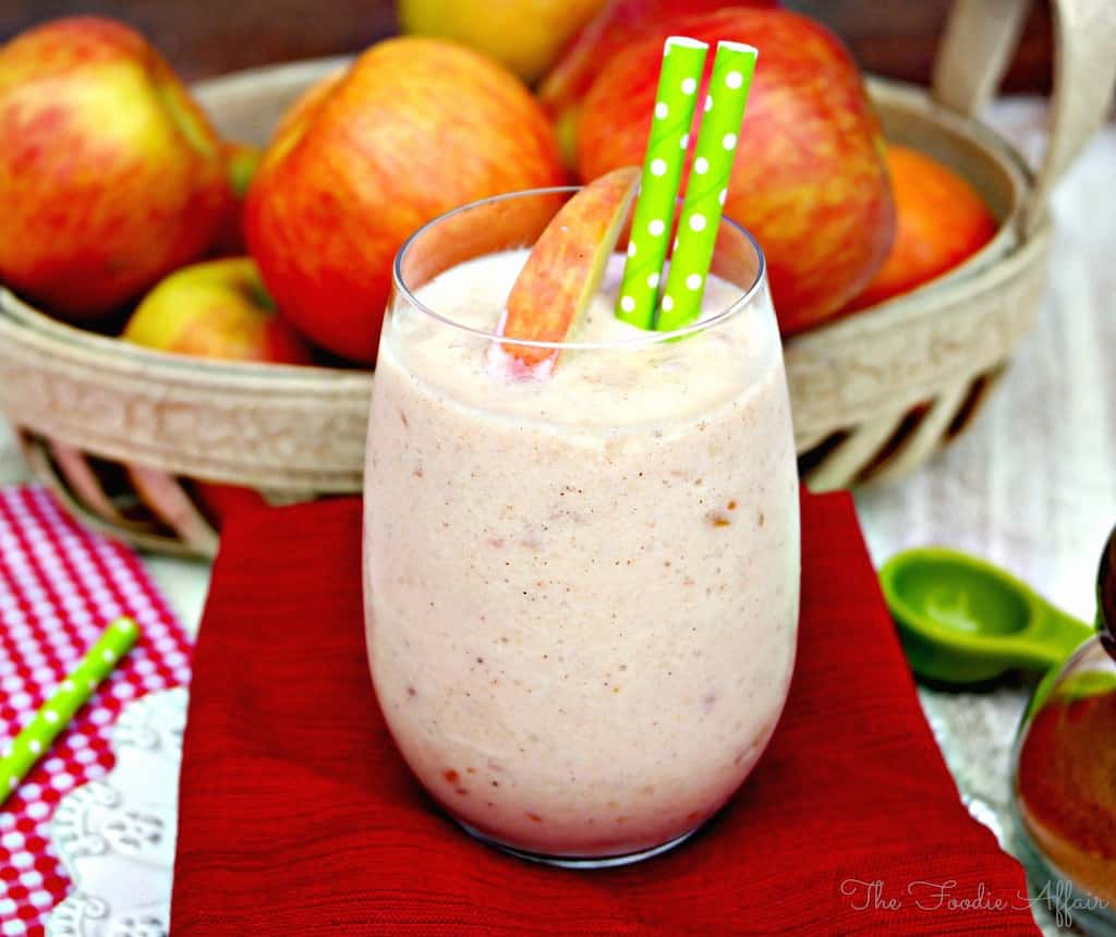 Apple Smoothie in a clear glass with fresh apples in a basket