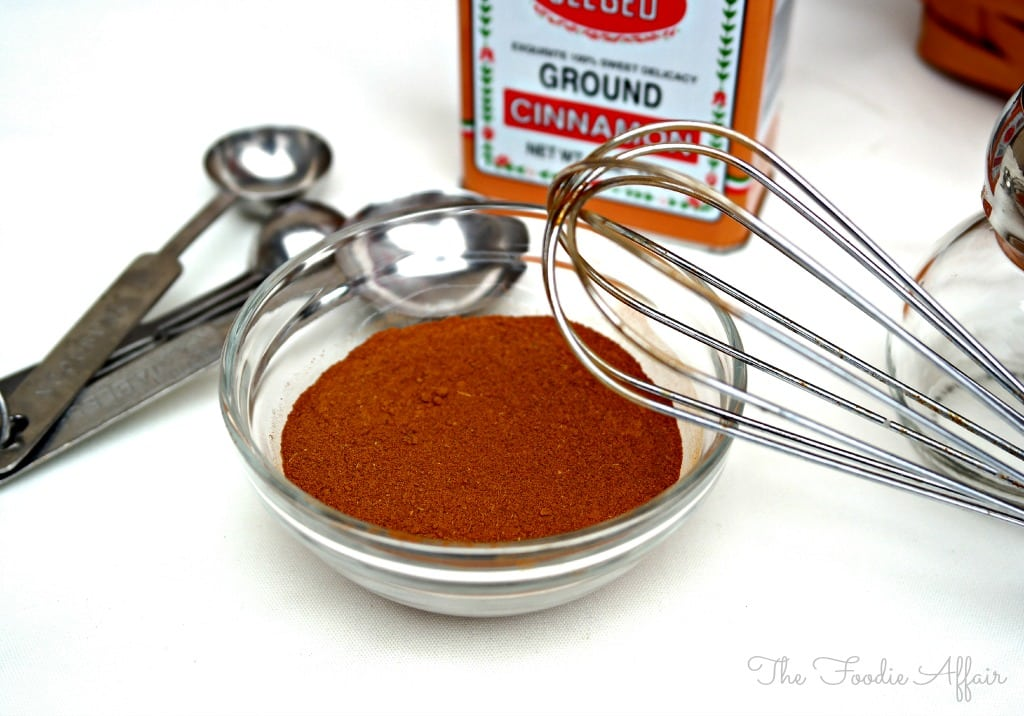 Apple Pie Spice Mix ingredients in a small glass bowl with a whisk on the side