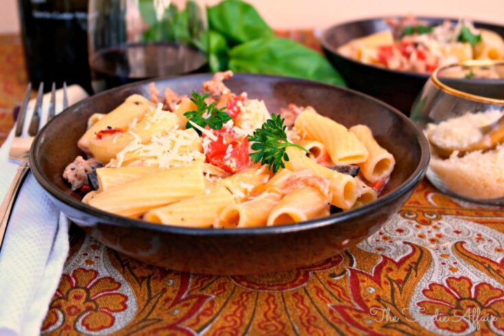 Italian Sausage Rigatoni in a brown pasta bowl topped with fresh basil.
