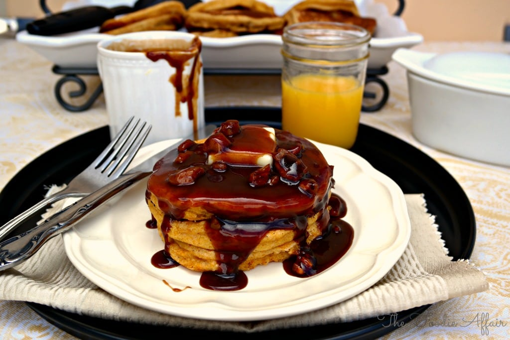 pumpkin pancakes on a white plate with a glass or orange juice on the side