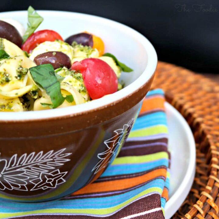 Tortellini Pesto Salad in a brown pyrex bowl.