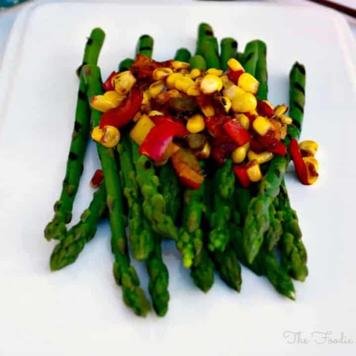 Asparagus with Sautéed Veggies on a white serving plate