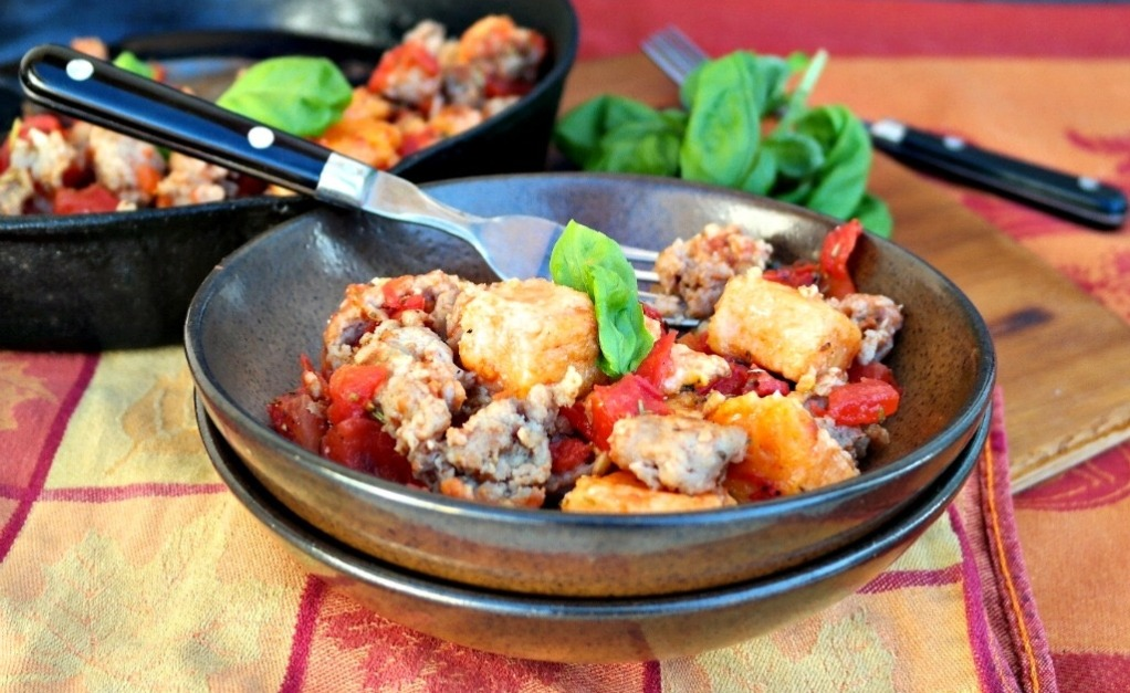 Homemade sweet potato gnocchi with sausage in brown serving bowls.