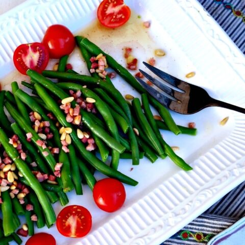 Fresh Green Beans with sliced tomatoes on a white platter