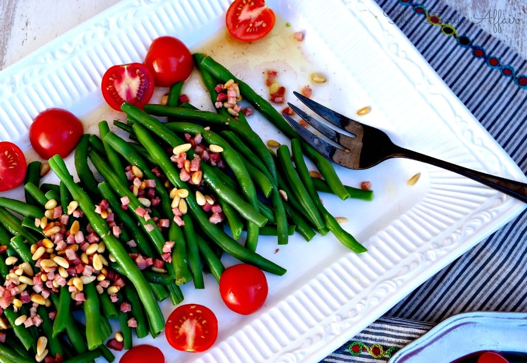 green bean recipe with pine nuts on a white platter