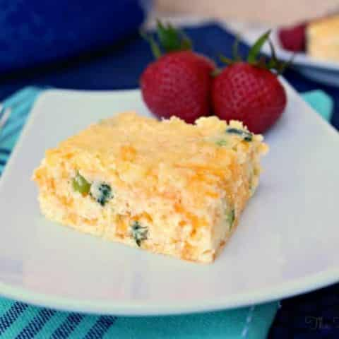 cheddar egg casserole on a white plate with strawberries