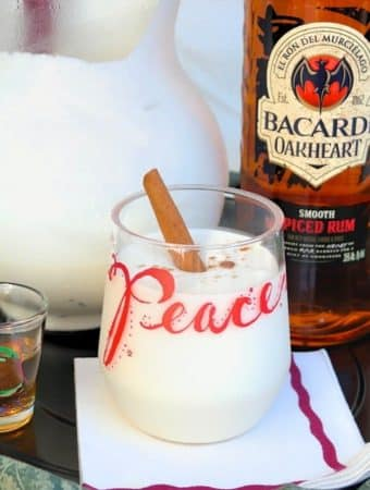 coquito cocktail in a clear glass with the words PEACE with rum on the side