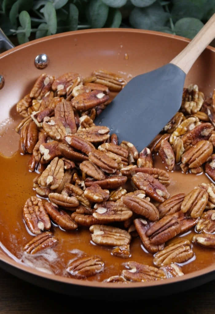 Warm skillet with maple syrup and pecans.