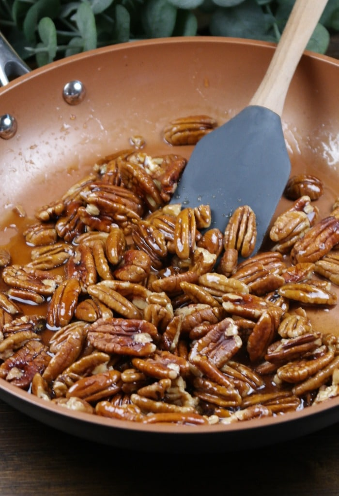Rubber spatula stirring pecans in maple syrup to carmelize.