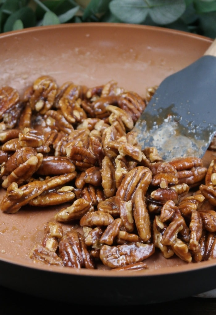 Caramelized pecans in a skillet pan.