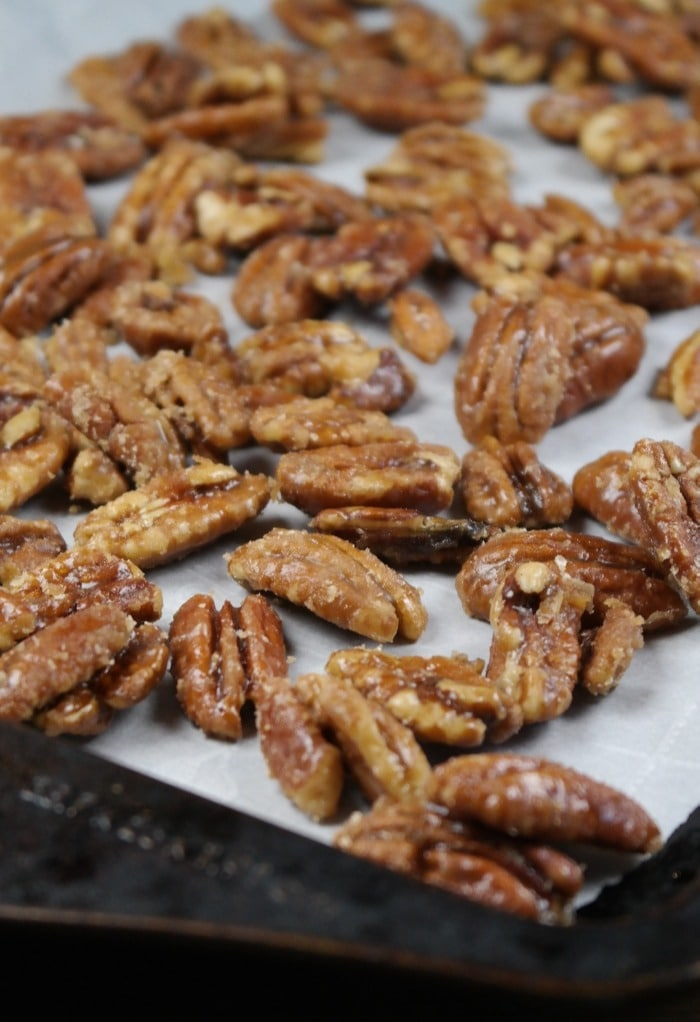 Cooling caramelized pecans on a baking sheet covered with parchment paper.