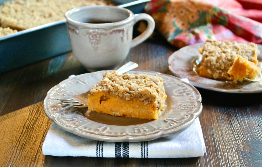Crumble cake made with sweet potatoes on a tan plate with a cup of coffee on the side.