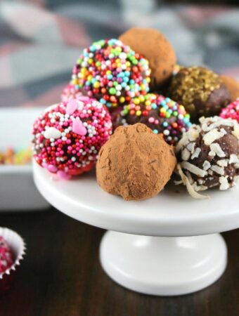 A mini white cupcake stand filled with chocolate truffles