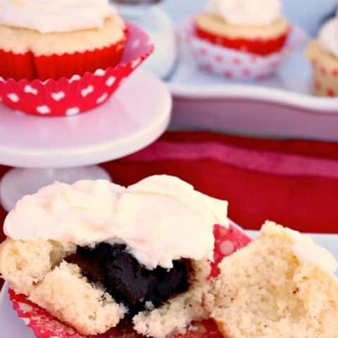 Fudge Filled Vanilla Cupcakes in a red baking cupcake liner