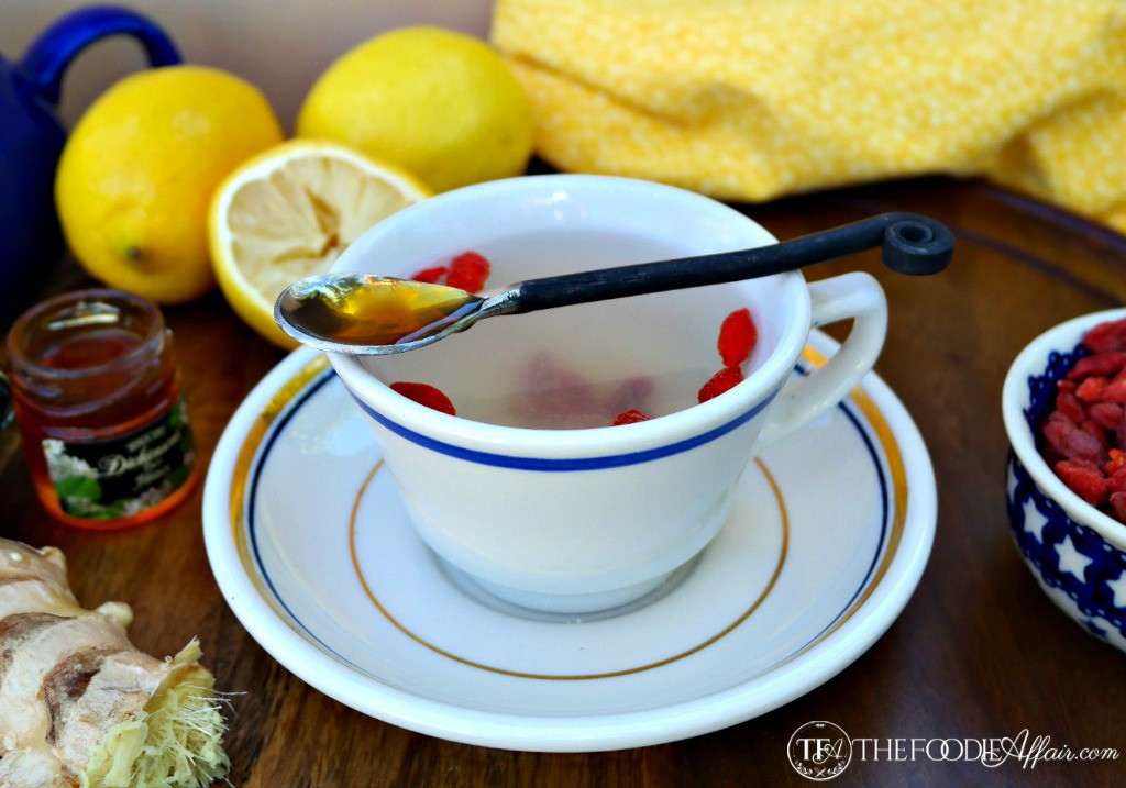 White teacup with blue rim of lemon ginger detox tea with a spoonful of honey