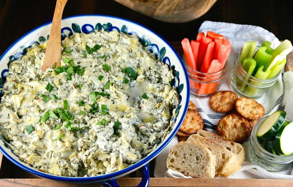 Horizontal shot of spinach dip with vegetables and crackers for dipping