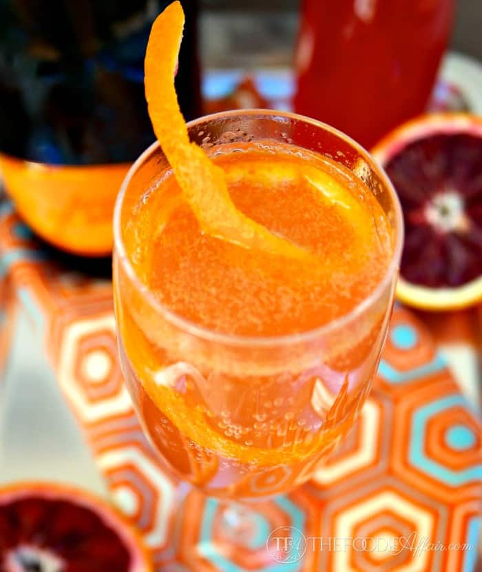French 75 recipe in a clear glass with blood orange