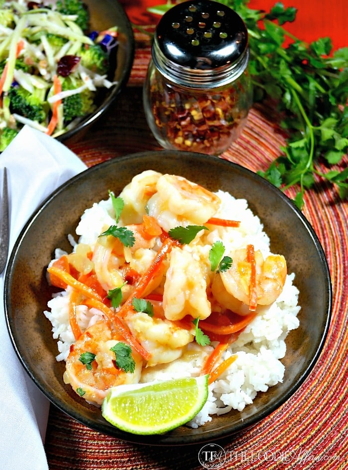 Shrimp in Coconut Sauce in a brown plate over rice with a side of vegetables