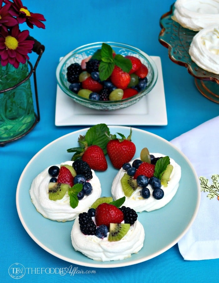Individual Pavlova Nests filled with fruit on a blue plate