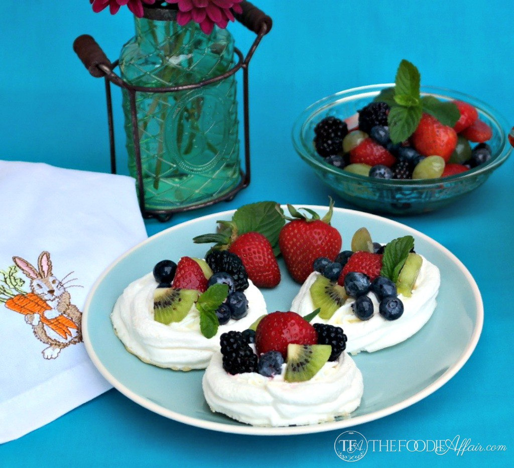 Small individual pavlova nests filled with fruit on a blue plate