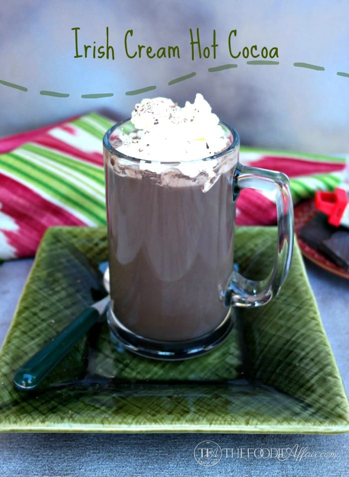 Irish cream hot cocoa in a clear mug on a green plate