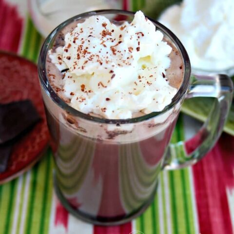 Irish Cream Hot Cocoa in a tall clear mug topped with whipped cream