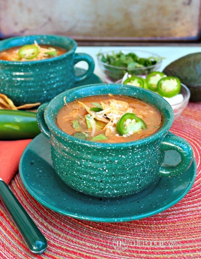 Slow cooker chicken tortilla soup in a green bowl on a red placemat