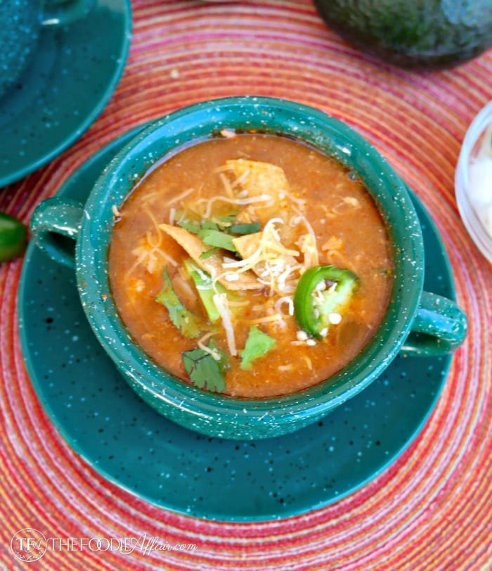 Slow cooker chicken tortilla soup topped with cheese, cilantro and sliced jalapenos
