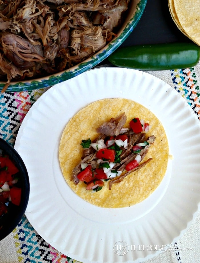 Slow Cooker Pork Carnitas with fresh salsa on a white paper plate