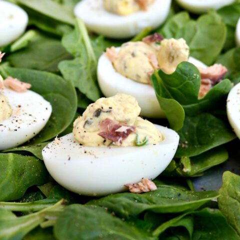 Smoked Salmon Deviled Eggs over a bed of fresh green spinach