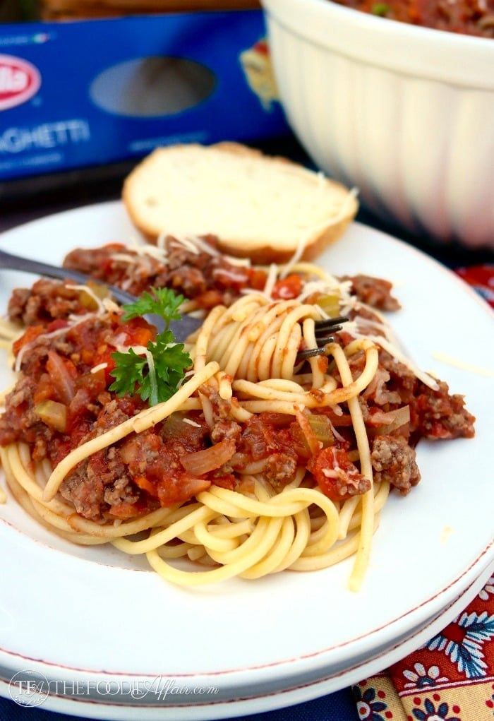 Spaghetti topped with meat sauce on a white plate