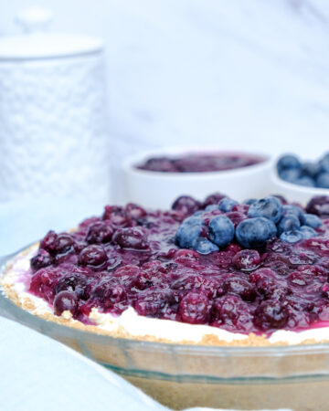 Homemade no bake blueberry cream cheese pie in a clear baking dish.