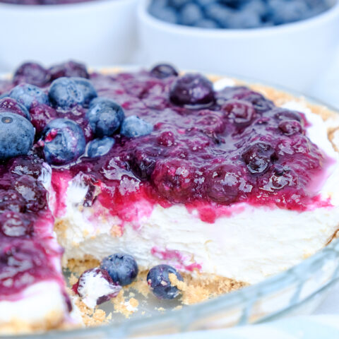 A slice removed from a no bake blueberry cream cheese pie.