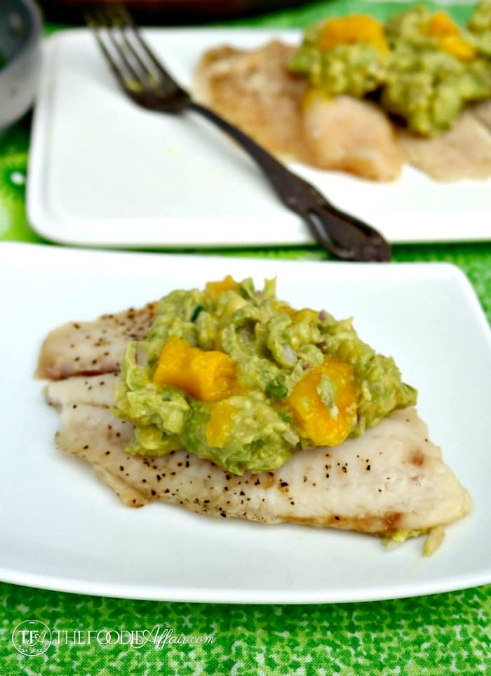 Tilapia fish topped with avocado and mango on a white plate