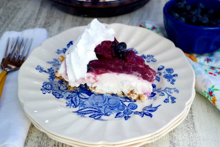 A slice of blueberry cream cheese pie on a blue and white plate.