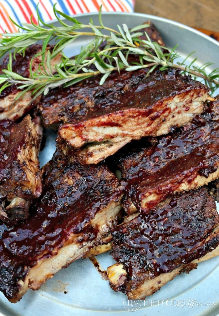 Baked ribs with blueberry bourbon sauce on a tin platter