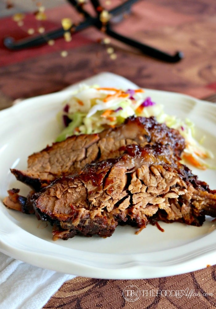 Oven cooked barbecue brisket slices on a white plate