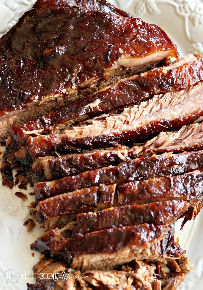 Oven cooked barbecue brisket sliced on a white platter