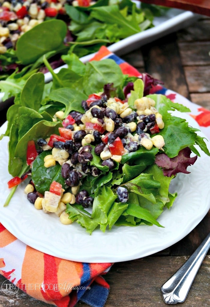 Black Bean and Corn Salad Recipe Over A Bed Of Greens on A White Plate