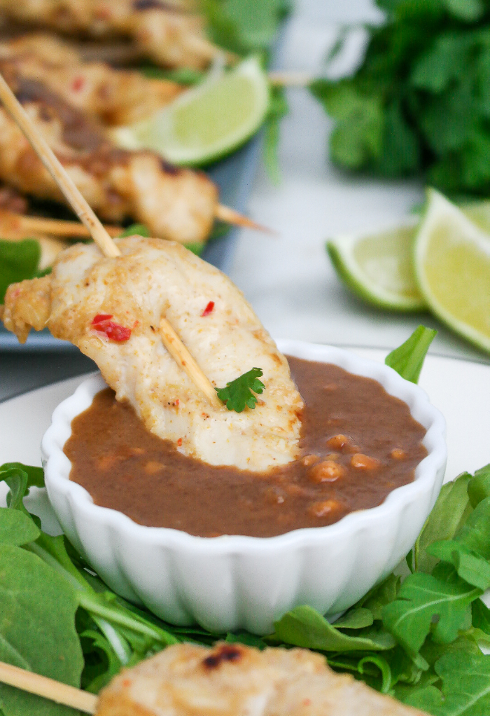 A small bowl of peanut sauce with chicken satay.