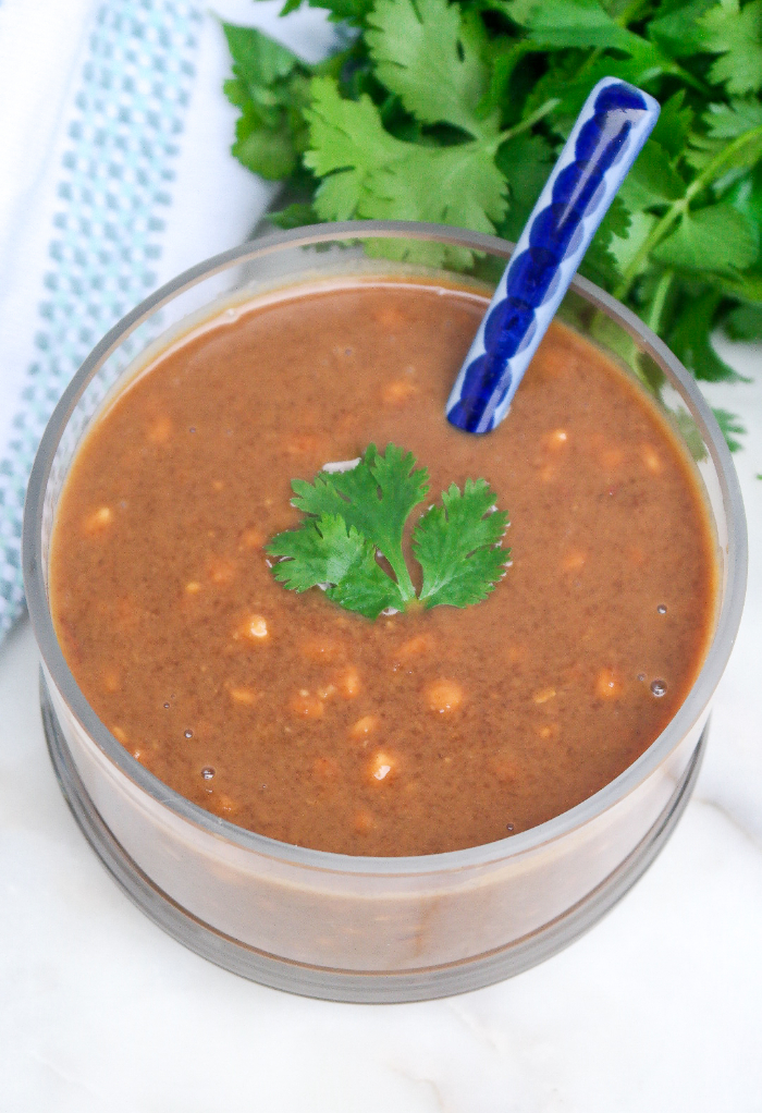 Thai peanut sauce in a clear serving bowl with a ceramic spoon.