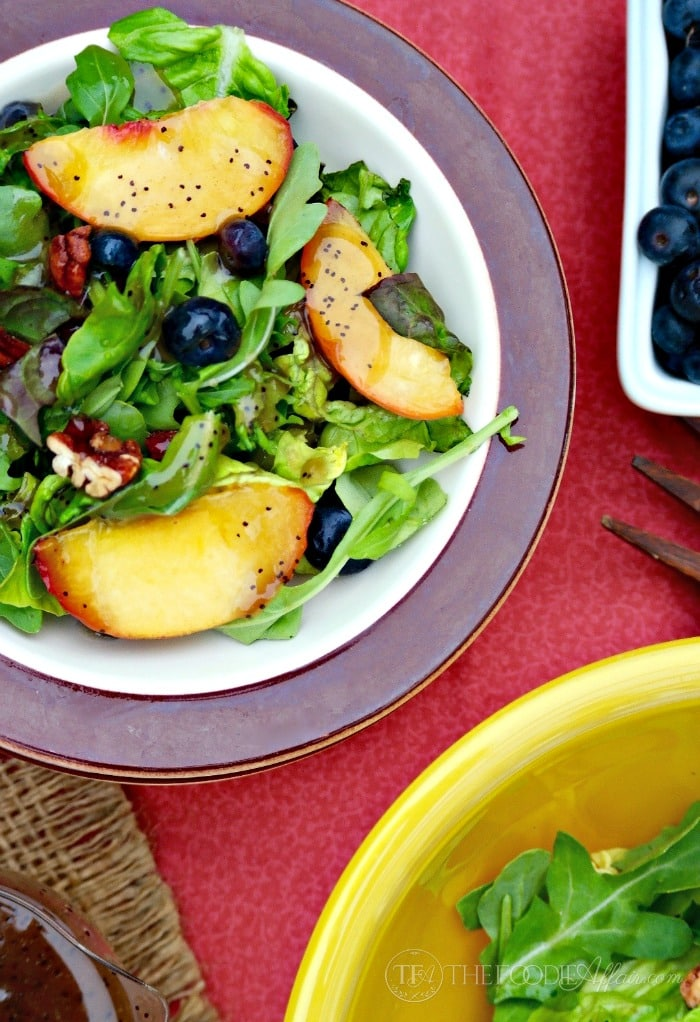 Salad with peaches and blueberries topped with light poppy seed dressing